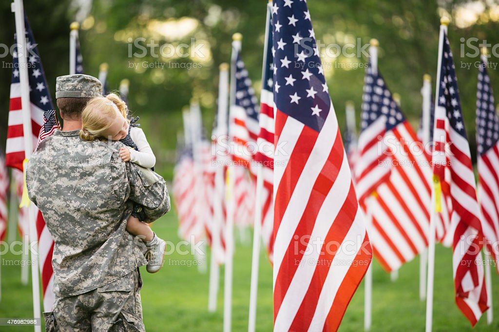 American soldier holding his toddler daughter stock photo