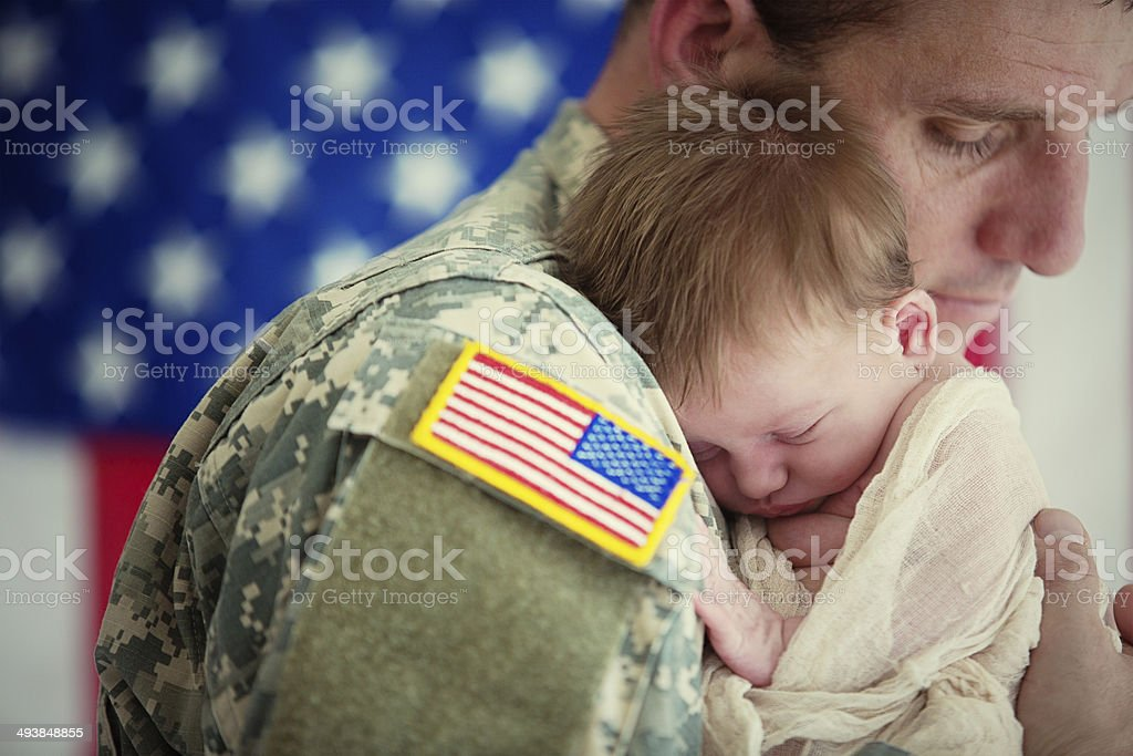 American soldier holding newborn baby stock photo