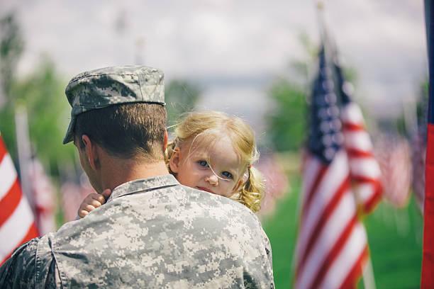 American soldier hugging his toddler daughter stock photo