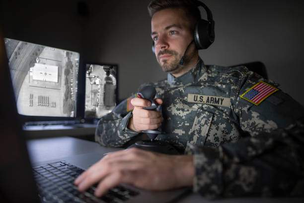 American soldier in headquarter control center initializing drone attack. Modern warfare. American soldier in headquarter control center initializing drone attack. Modern warfare. us military stock pictures, royalty-free photos & images