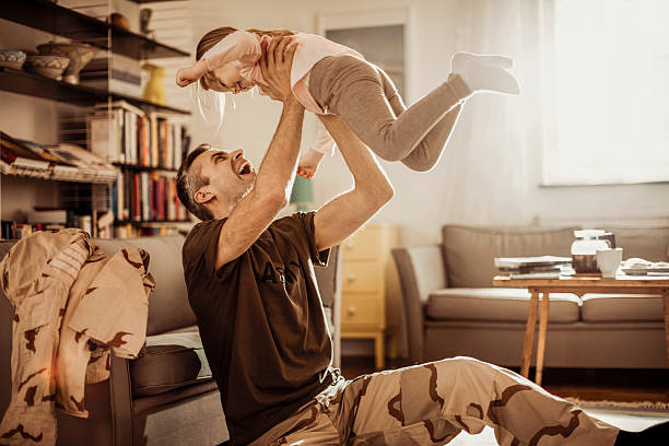 American soldier playing with his daughter Photo of American soldier playing with his daughter at home military lifestyle stock pictures, royalty-free photos & images