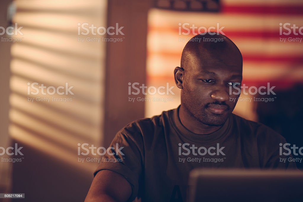 American soldier using laptop stock photo