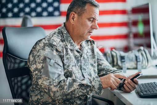 One mature man, American soldier sitting in headquarters office alone, using smart phone.