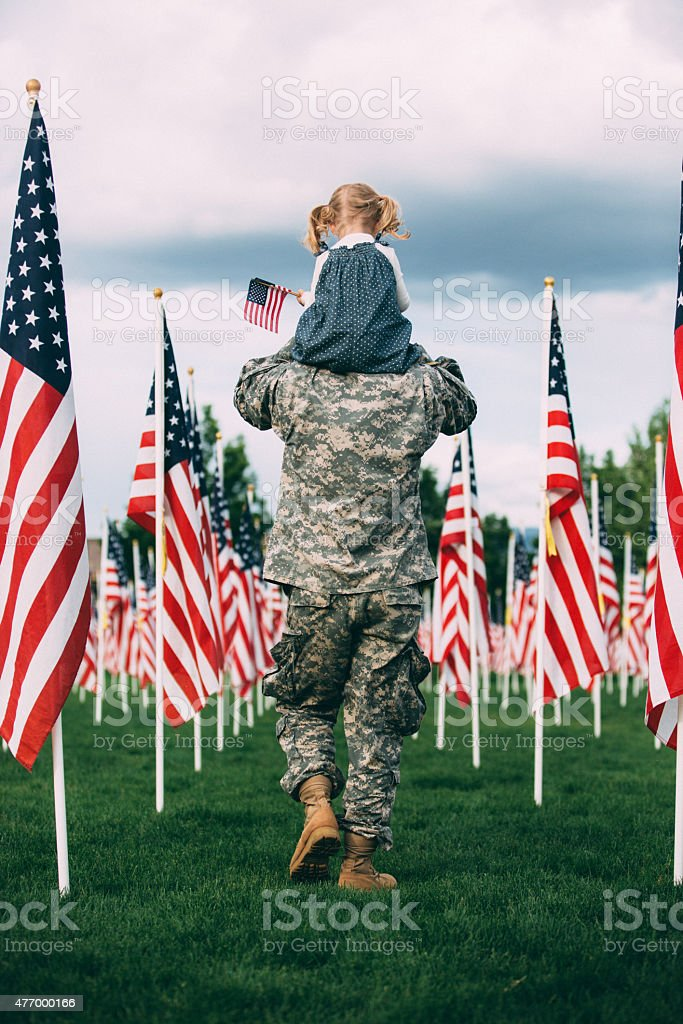 American soldier walking with his daughter on his shoulders stock photo