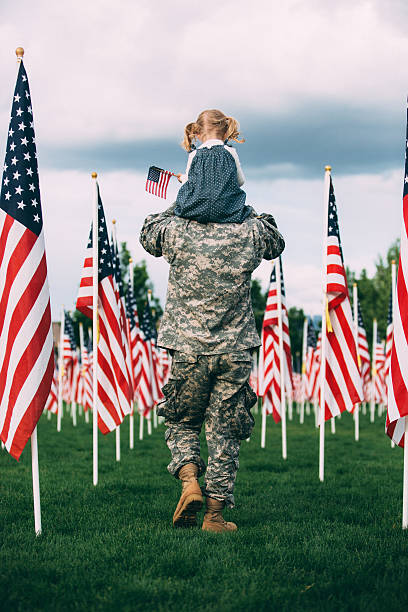 American soldier walking with his daughter on his shoulders Rearview of American soldier carrying his toddler daughter on his shoulders, They are walking in a field of American flags. independence day photos stock pictures, royalty-free photos & images