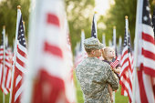 American soldier looking at flags with his daughter