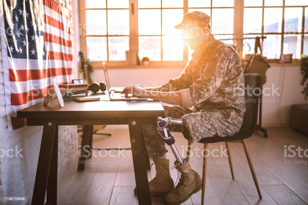 American soldier with prosthetic leg working in his office Young Soldier in uniform with amputee leg sitting on desk in office, using lap top 20-29 Years Stock Photo
