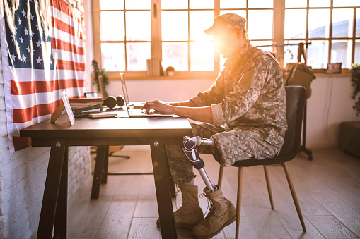 American Soldier With Prosthetic Leg Working In His Office Stock Photo - Download Image Now
