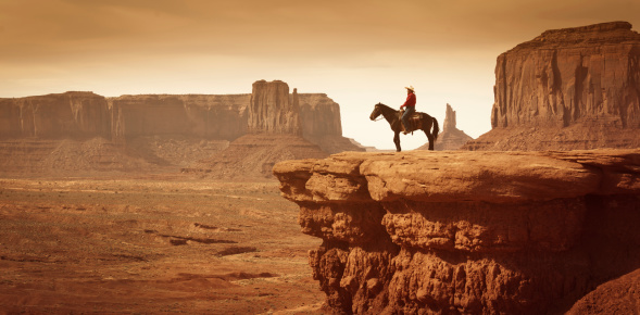 Subject: A native American Indian cowboy riding a horse in a desert landscape with plateaus in the distance.