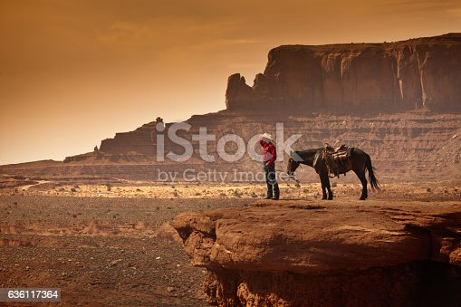 A retro sepia toned portrait of a wild west cowboy on horse back. Photographed in the American southwest, the Monument Valley Tribal Park. in Arizona, USA. Photo in panoramic horizontal format with copy space.
