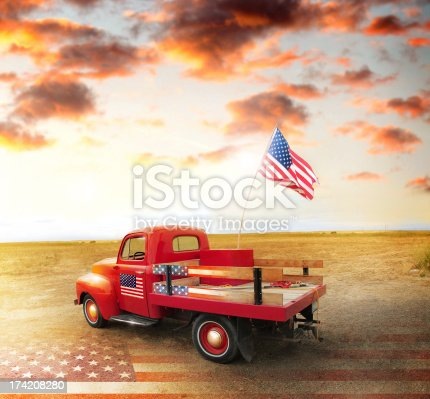 Red vintage pick up truck with American flag in wide open country side with dramatic sunset cloudscape and US flag on ground