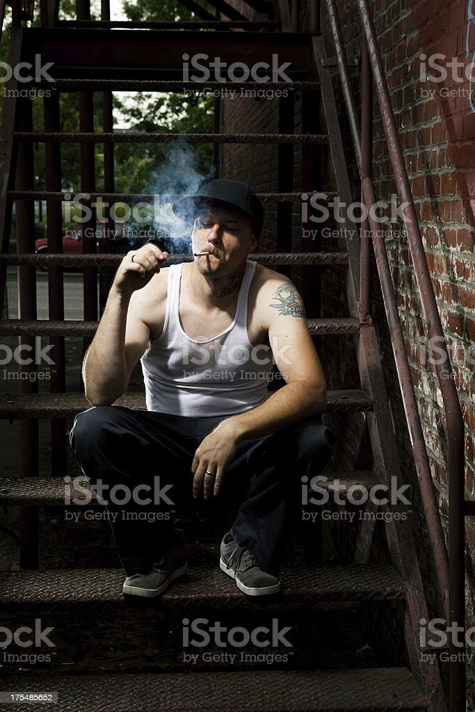 American Tough Gangster Thug Man Smoking Cigarette in Alley stock photo