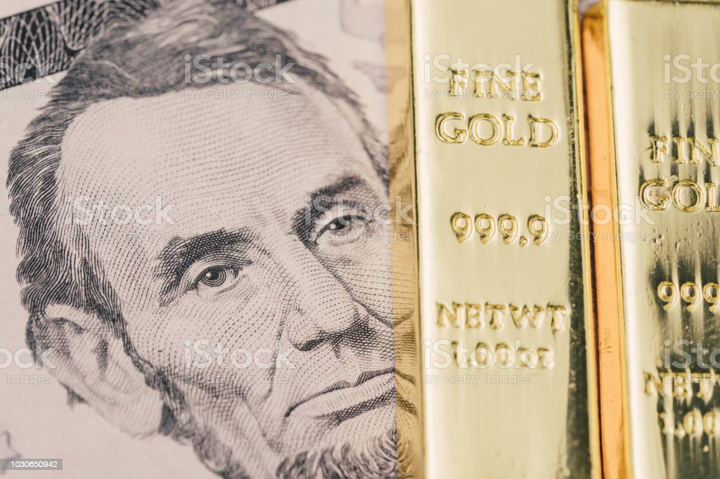 American US dollar banknote money with shiny ingot of gold bar, bullion as financial asset, safe haven of investment and wealth concept stock photo