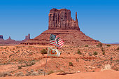 Monument Valley, Arizona, USA. Photo taken 06/01/2018. American USA flag and Navajo flag waving in monument valley