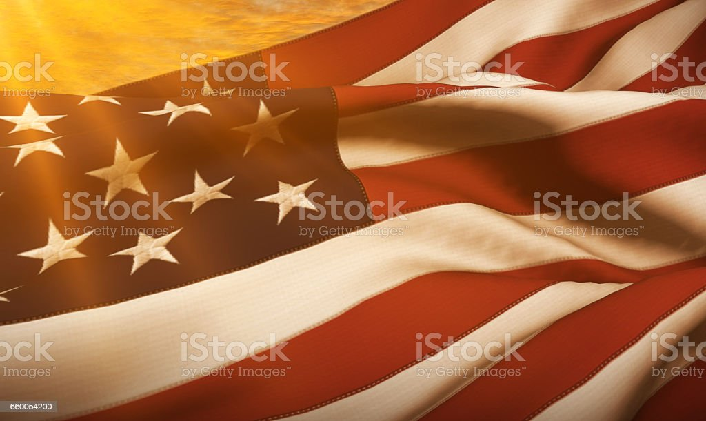 american USA flag, stars and stripes at sunset, with sun rays light stock photo