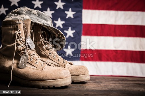 USA military boots, hat and dog tags with American flag in background.  No people in this US Memorial Day or Veteran's Day image.