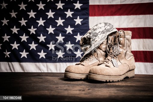 istock American Veteran's Day theme with military boots, hat, USA flag. 1041862048