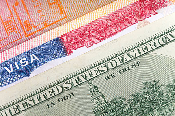 American visa on page of  international passport and US dollars,