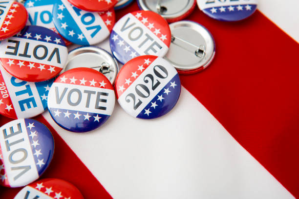 american vote badges on national usa flag background - vote стоковые фото и изображения
