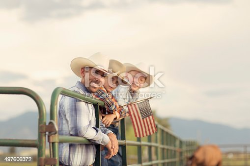 An American father and sons in western wear take a portrait on their farm in Utah. They are quintessential cowboys and cowgirls standing on a ranch gate holding a USA flag.