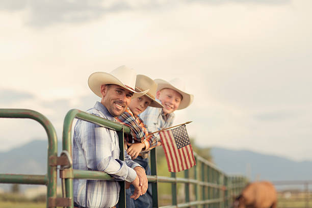 American West Boys dressed Holding USA Flag An American father and sons in western wear take a portrait on their farm in Utah. They are quintessential cowboys and cowgirls standing on a ranch gate holding a USA flag. family 4th of july photos stock pictures, royalty-free photos & images