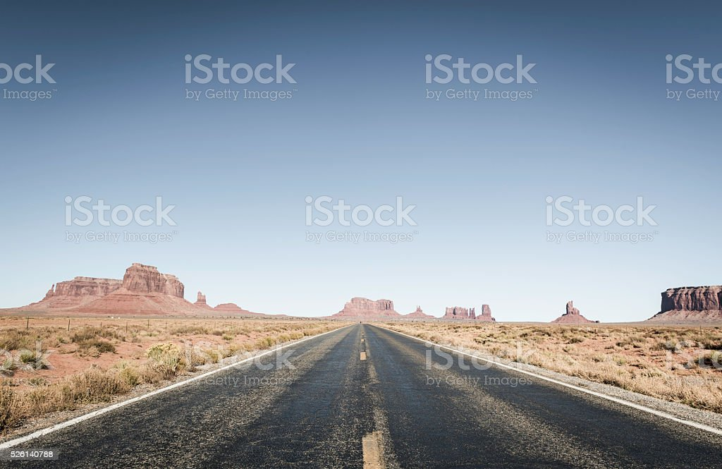 American West long straight desert road through Monument Valley Utah Long straight road arrowing through the desert sandstone of the Colorado Plateau to the iconic mesas of Monument Valley deep in the rural landscape of southern Utah. ProPhoto RGB profile for maximum color fidelity and gamut. Accidents and Disasters Stock Photo
