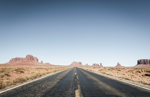American West Long Straight Desert Road Through Monument Valley Utah Stock Photo - Download Image Now