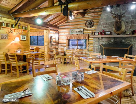 American Western log cabin restaurant dining room interior with a stone fireplace,deer head trophy, pickled vegetables and pictures on the wall.