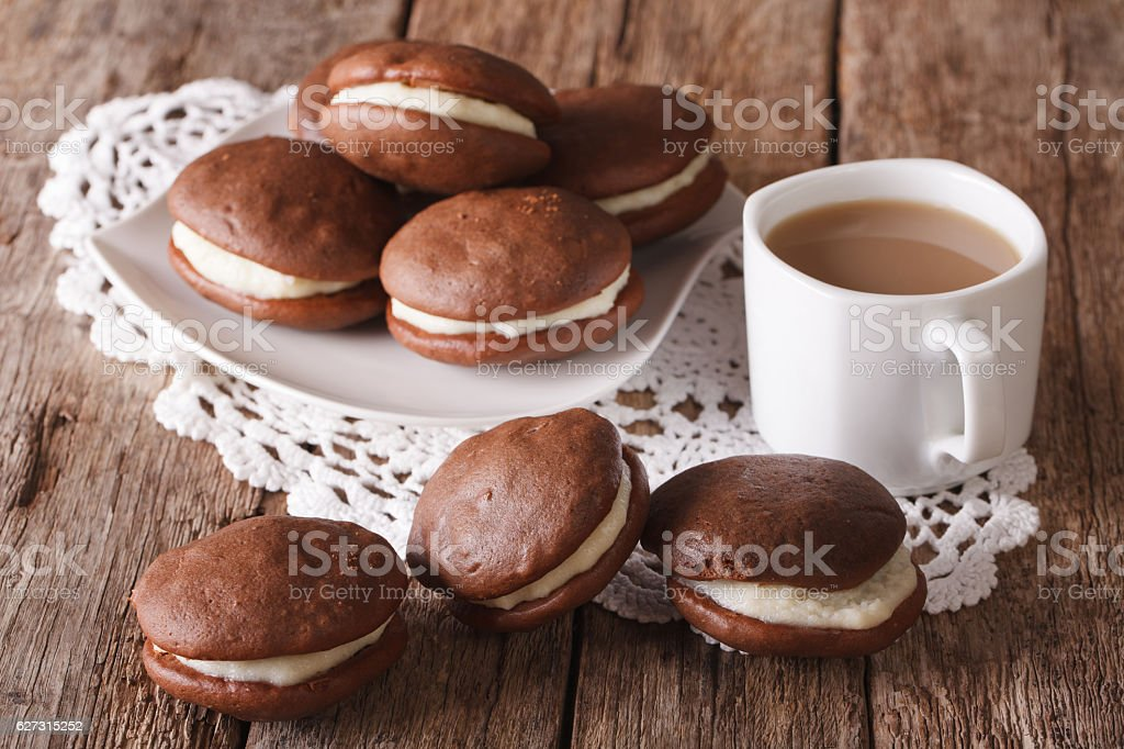 American Whoopie pie pastry and coffee with milk close-up. horizontal stock photo