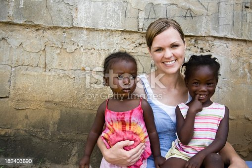 An American woman holding two African girls.