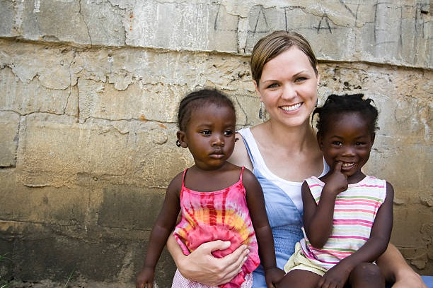 American Woman Holding African Girls stock photo