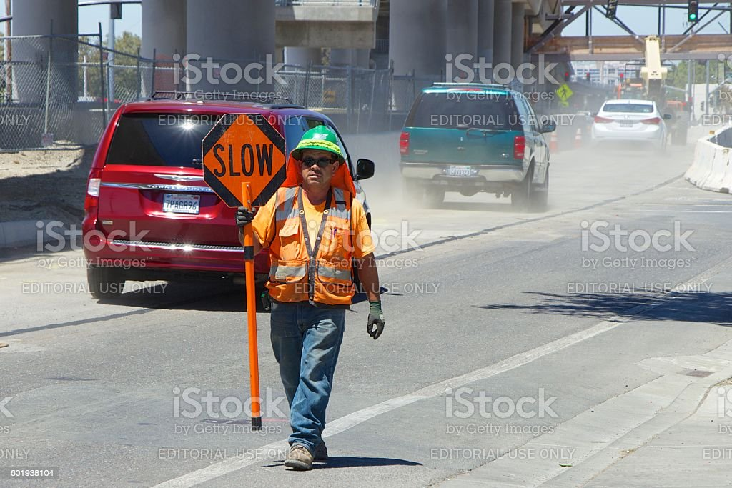 American worker in an orange vest shows a sign 'Slow' stock photo