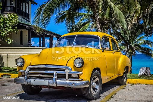 HDR - American beautiful yellow vintage cars parked under palms in Varadero Cuba - Serie Cuba Reportage