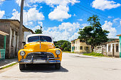 American yellow vintage car parked on the street before a building in Sagua la grande in the countryside from Cuba - Serie Cuba Reportage