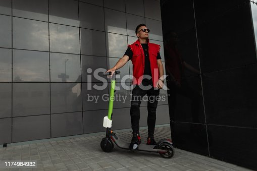 American young hipster man with a hairstyle in stylish denim red-black clothes in sunglasses stands with a modern electric scooter near a dark wall in the city. Cool guy model is resting outdoors.