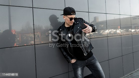 American young man hipster in a black leather jacket in a baseball cap in jeans in a t-shirt is standing near the modern building in the city and takes a selfie. Stylish guy enjoys the weekend. Youth.
