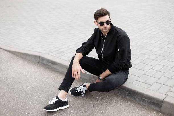 american young man model in een modieuze jas in zwarte jeans in sneakers in dark zonnebril zit op de tegel op een straat in de zomerdag. moderne guy hipster rust in de stad. herenkleding - zwarte spijkerbroek stockfoto's en -beelden