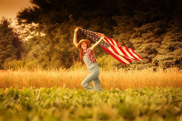 Americana Farm Girl with U.S. Flag on 4th of July stock photo