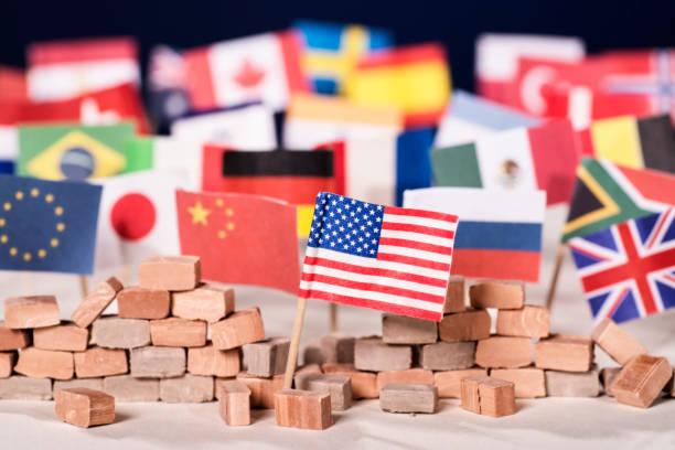 Amerikanische Flagge und Mauer Amerikanische Flagge vor einer Mauer und Flaggen anderer Länder foreign affairs stock pictures, royalty-free photos & images