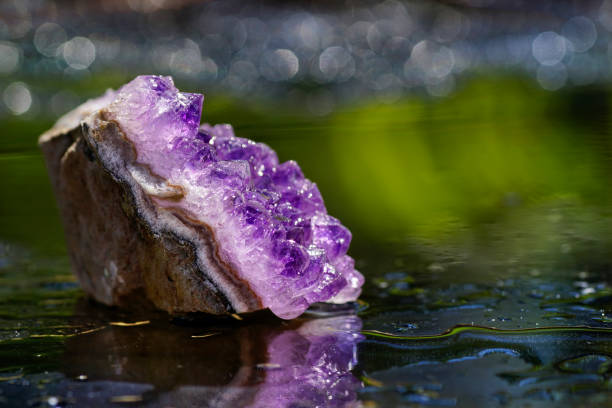 Amethyst quartz mineral, reflection in the water, defocused background stock photo