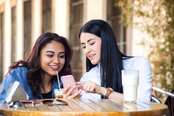 Amigas tomando café, viendo el celular stock photo