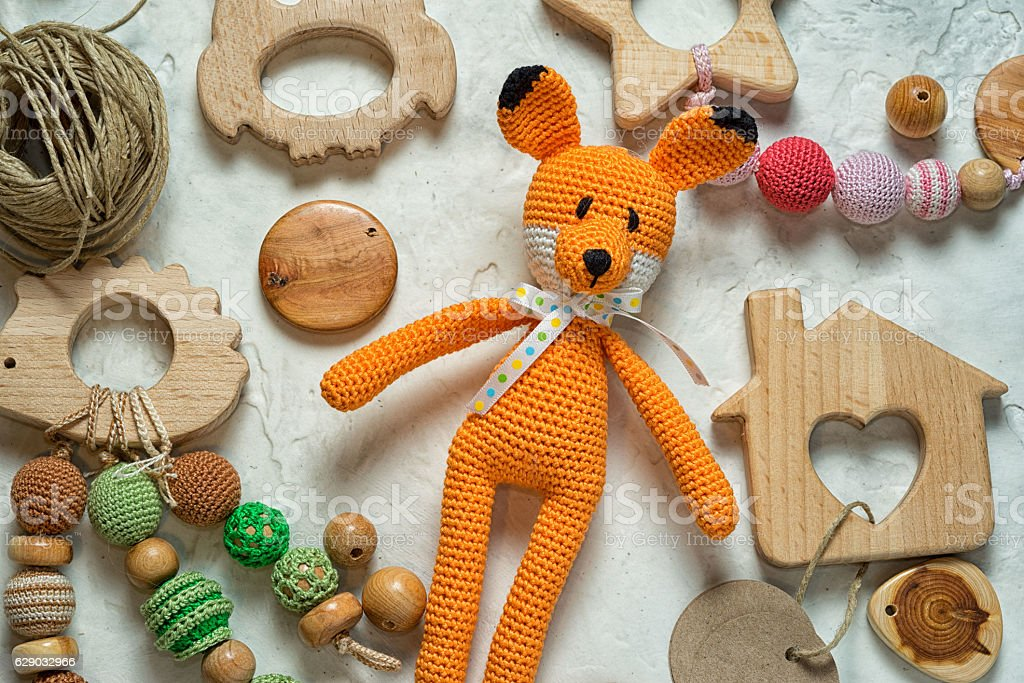 amigurumi fox toy laying among mess wooden toys and beads - foto de stock