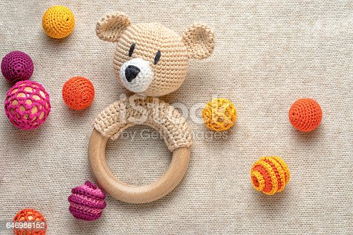 amigurumi toy bear and crocheted beads on a knitted background with copy space
