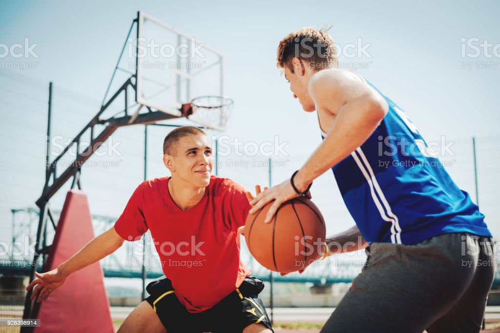 Two guys playing basketball on outdoors court in summer. Teenager and...
