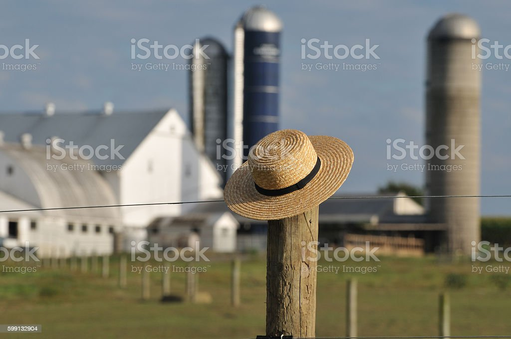 Amish farm with straw hat over fence post stock photo