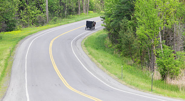 Amish Horse and Buggy on Rural Highway Road A solitary Amish horse and buggy on a rural highway heads around the curve on an obviously often-traveled carriage route with many buggy wheel track markings in the Adirondacks region of northern New York state. anachronistic stock pictures, royalty-free photos & images
