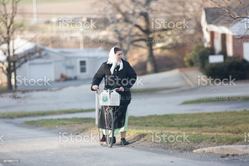 Amish women hand pushing a bicycle stock photo