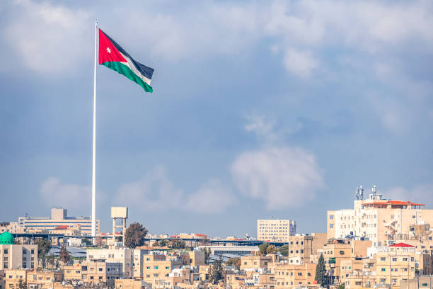 02/18/2019 Amman, Jordan, the flag of Jordan on the background of the gloomy sky walks in the wind above the capitals of the capital of the Middle Eastern state stock photo