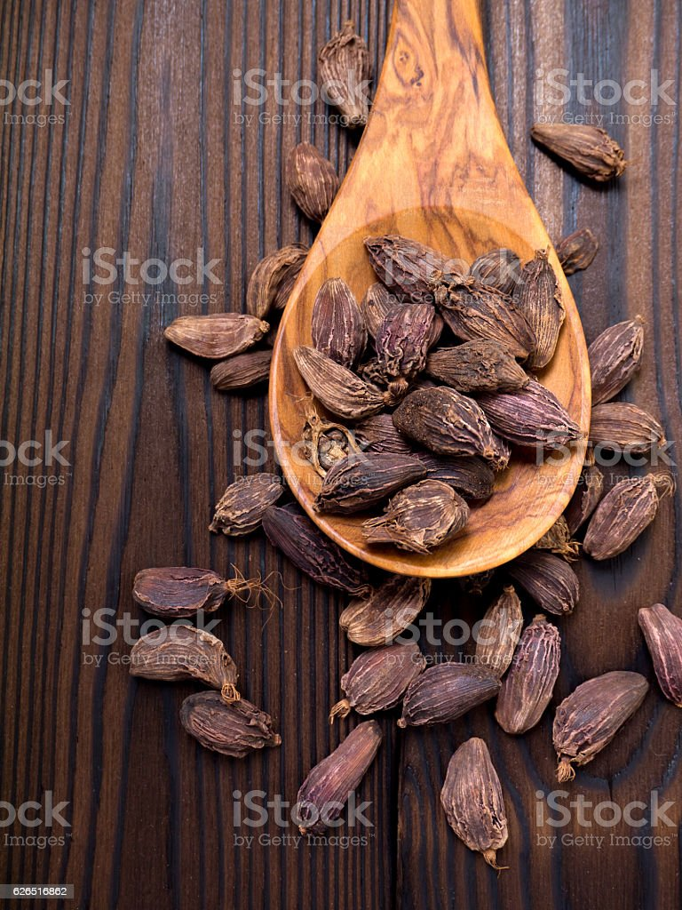 Amomum pods in the wooden spoon stock photo