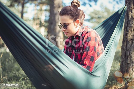 View of a beautiful young woman who's sitting in a hammock on a fresh summer day. She's wearing a lumberjack shirt, ready to explore the woods afterwards.